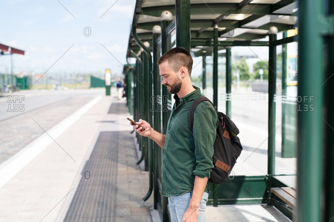 Profile view of man with facial hair checking phone at train station