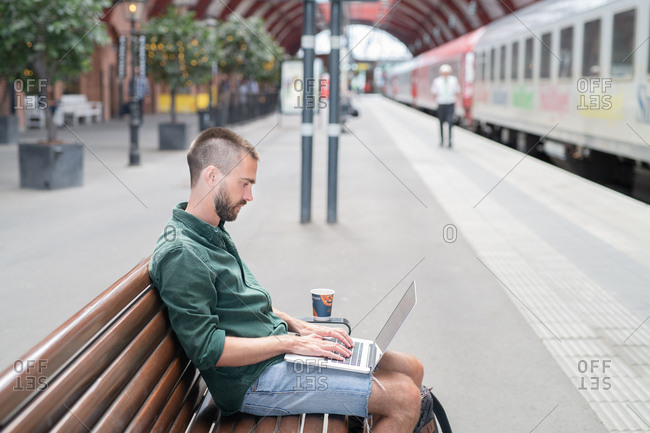 Side view of young man studying  laptop at park bench