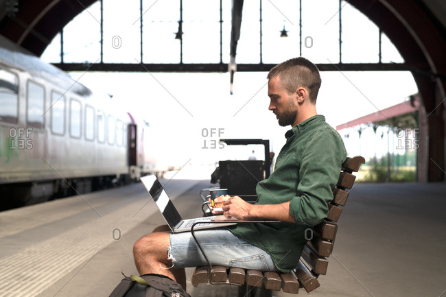 Man casually drinking coffee on wooden bench at transition