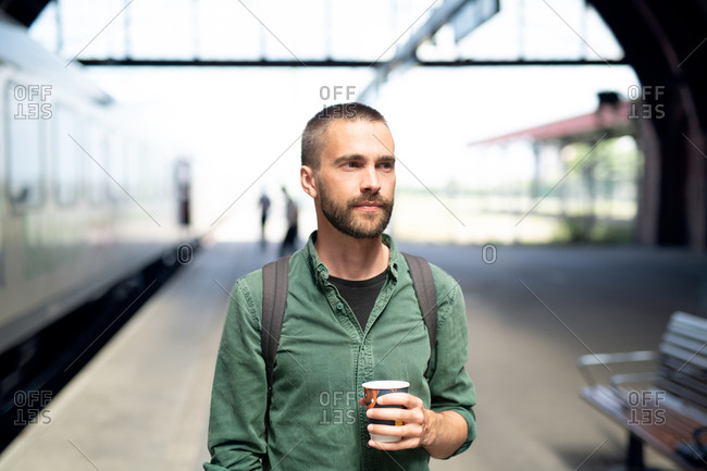 Young man holding cup of coffee at bus station