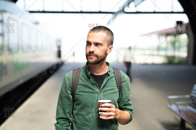 Young man with beard smirking with coffee in his hand