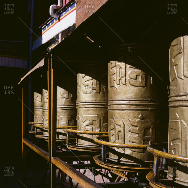 Row of Buddhist prayer wheels in hard sunlight