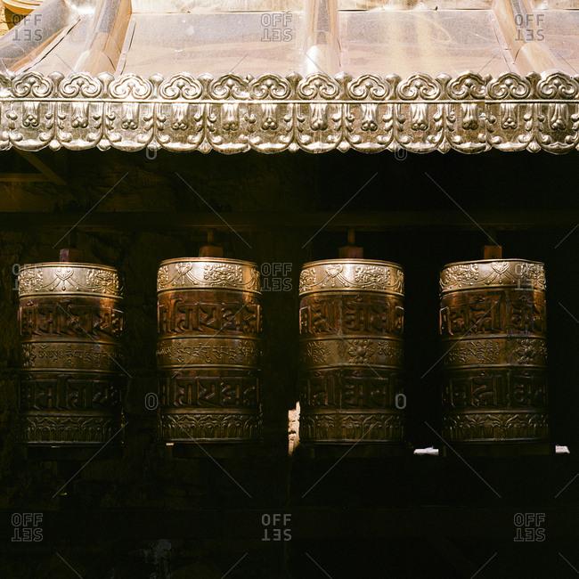 Buddhist prayer wheels glowing in sunlight