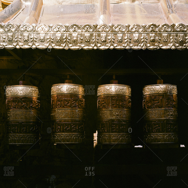 Buddhist prayer wheels glowing in sunlight