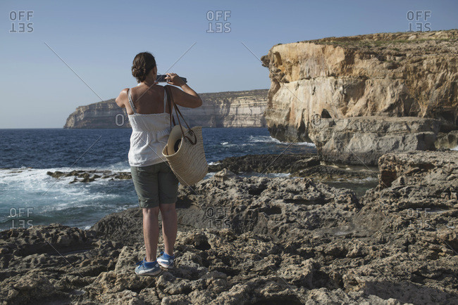Rearview of woman standing on rocks taking photo of sea cliffs with smartphone