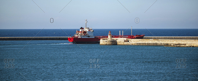 Large ship leaving harbor on bright summer day