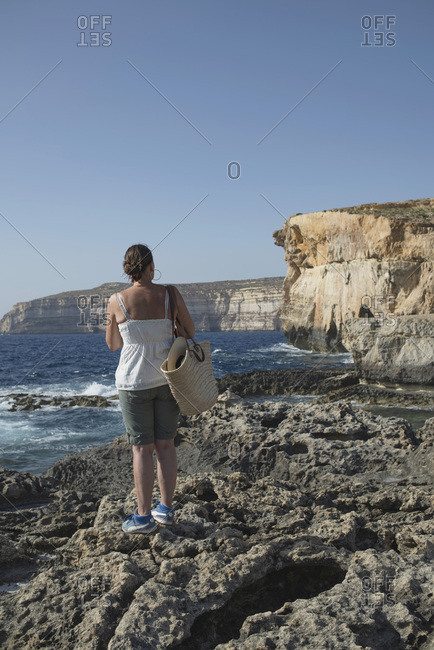 Rearview of woman standing on rocks by sea looking at cliffs