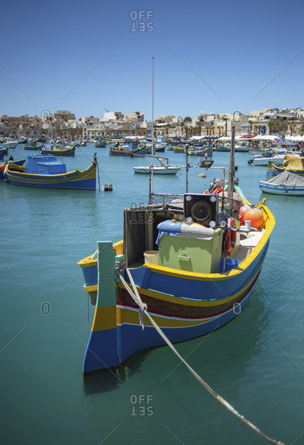 Colorful traditional wooden boats moored in harbor with view of waterfront in background