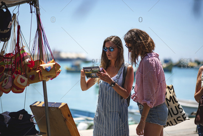 Marsaxlokk, Malta - June 10, 2018: Tourists looking at souvenirs at a stall by the port