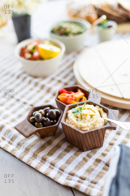 Hummus, olives, and peppers in bowls