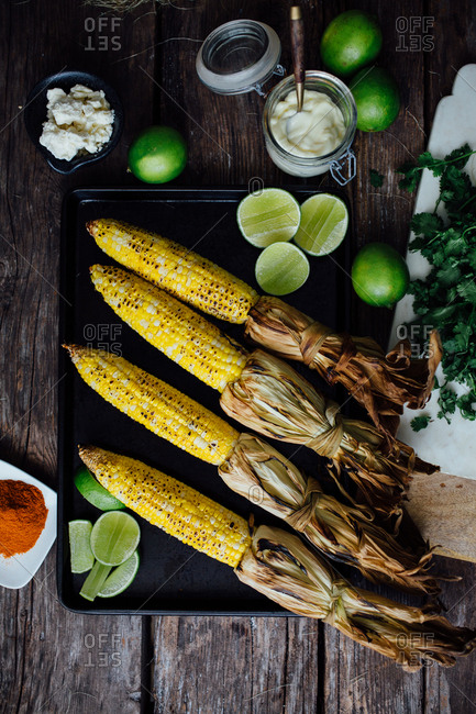 Grilled corn on pan with toppings