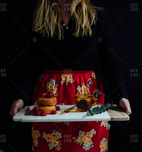 Woman in apron holding tray with donuts