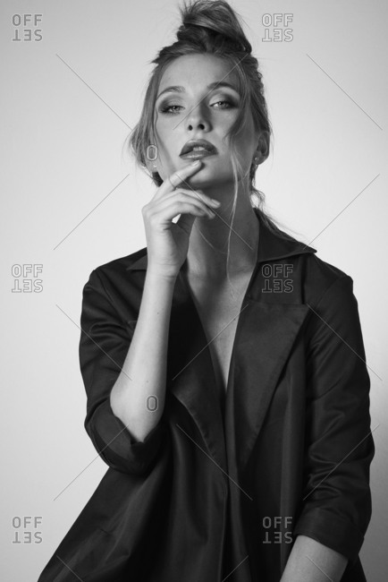 Black and white studio shot of woman posing with hand on chin