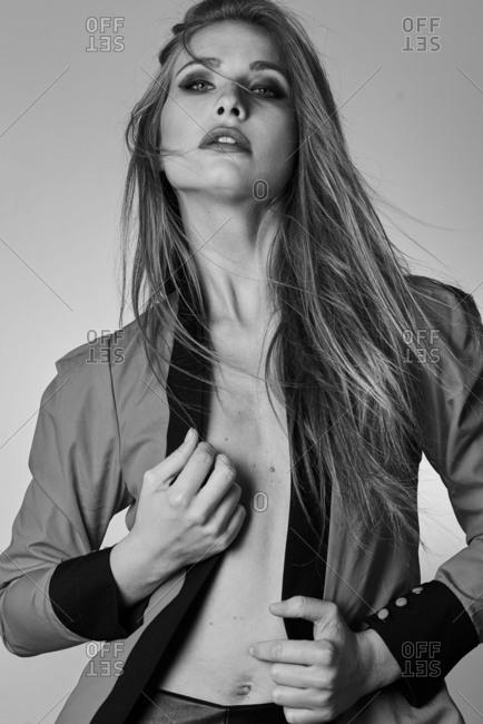 Model posing in studio with windblown hair wearing jacket