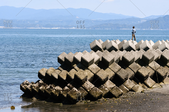 Kagoshima, Japan - March 26, 2016: A man stands atop a wave-breaking structure