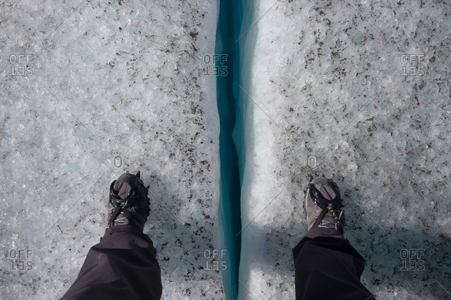 Seward, Kenai Fjords National, Alaska, United States of America - July 12, 2016: A hiker stands over an ice crevasse at Godwin Glacier in Kenai Fjords National Park