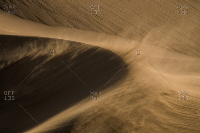 Strong desert winds blow sand over large sand dunes
