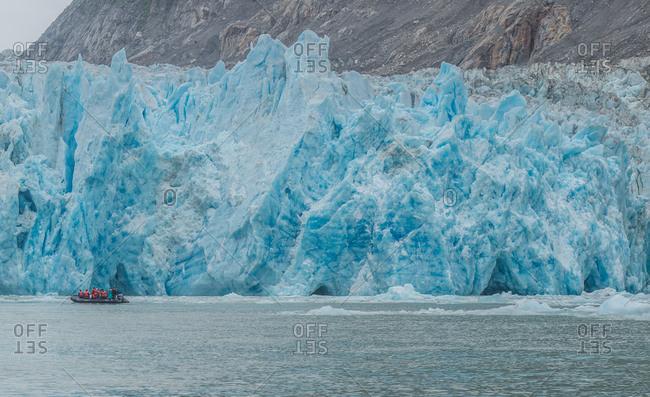 A tour boat navigates alongside a calving glacier