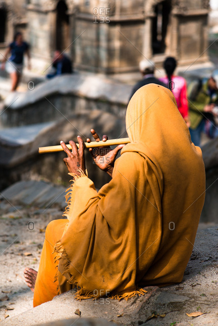 A musician in yellow garb plays flute at a temple site