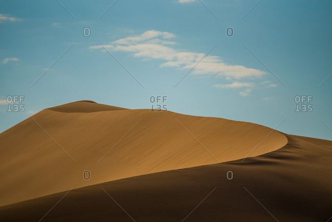 A large sand dune curves under a cloud in the desert