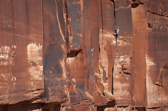 A male rock climber in colorful clothing ascends a crack climb known as Chasin skirt in midday