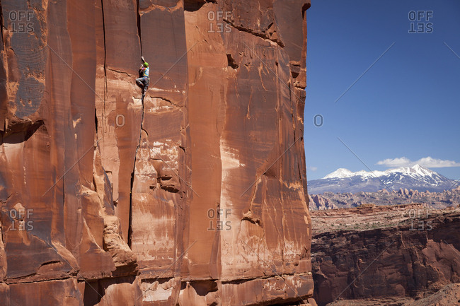 A male rock climber in colorful clothing ascends a crack climb known as Chasin skirt above the Colorado River in front of the La Sal mountains