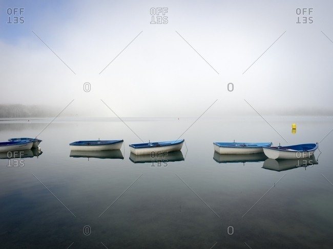 Boats rest on a fog-shrouded lake
