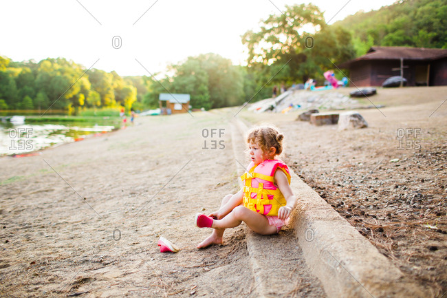 Little girl wearing bright colored life vest on a beach