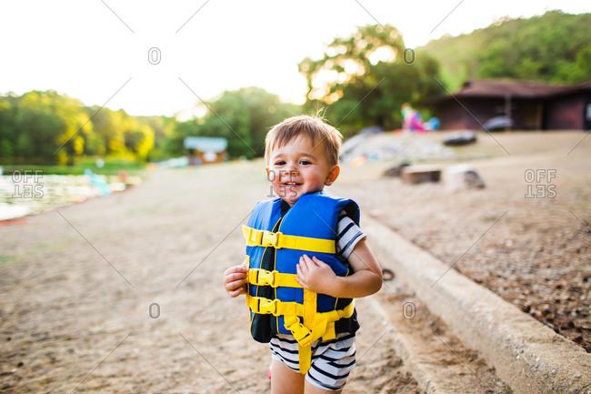 Little boy wearing life vest on a beach