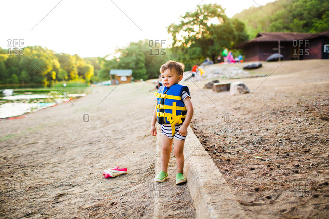 Toddler boy wearing life vest on a beach