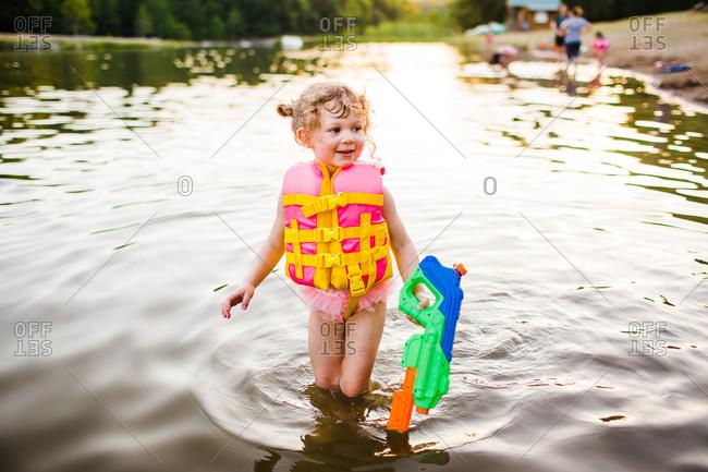 Girl with water gun in a lake