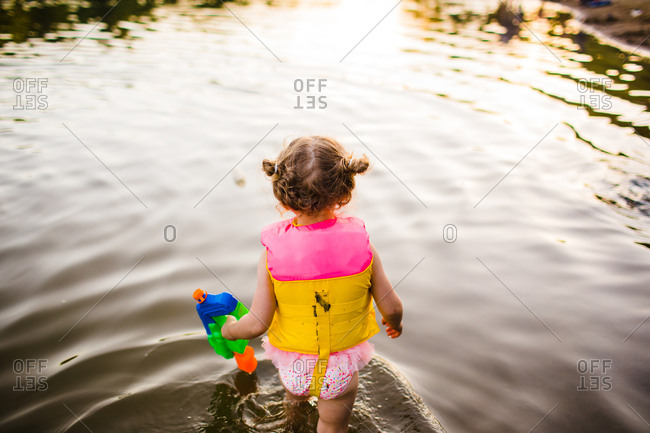 Rear view of girl with water gun in a lake