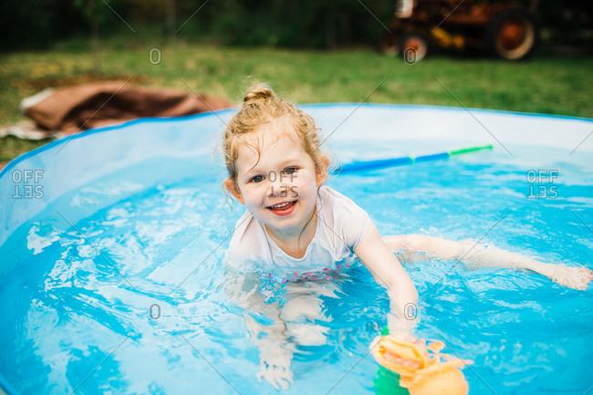 Little girl in backyard kiddie pool