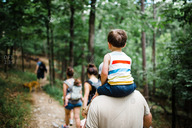 Father carrying son on his shoulders through the woods