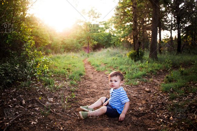 Little boy sitting on a trail in a forest