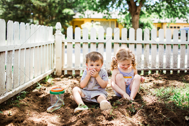 Two kids looking for bugs in the dirt