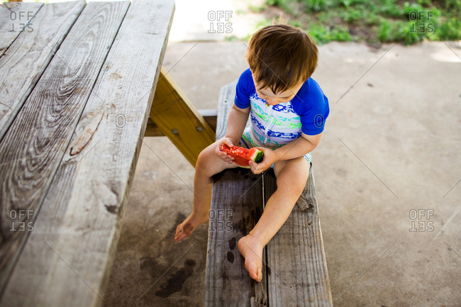Young boy eating watermelon at a picnic table