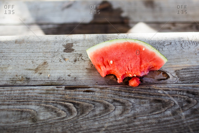 Slice of watermelon on a picnic table missing bites