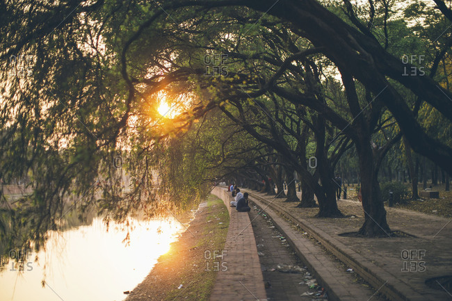 Dhaka, Bangladesh - February 17, 2014: Locals relaxing alongside a river lined with trees at sundown