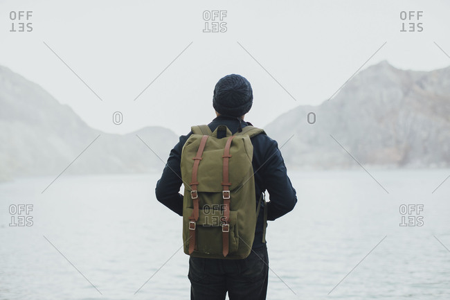 Rearview of man carrying backpack looking out over misty lake