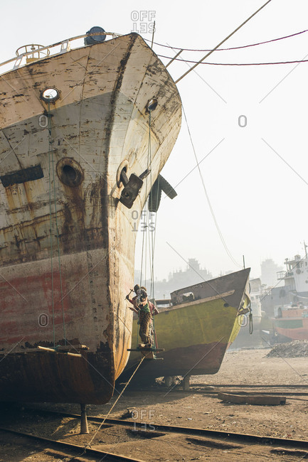 Workers suspended by ropes working on hull of ship in shipyard in Bangladesh