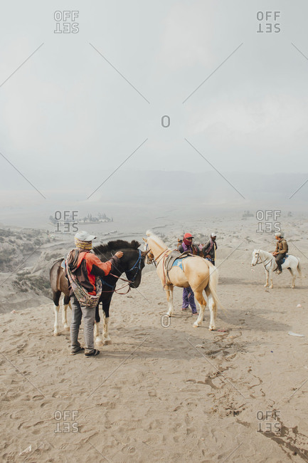 Mount Bromo, Indonesia - September 13, 2015: Tourists prepare to mount their ponies in sandy terrain of Bromo National Park