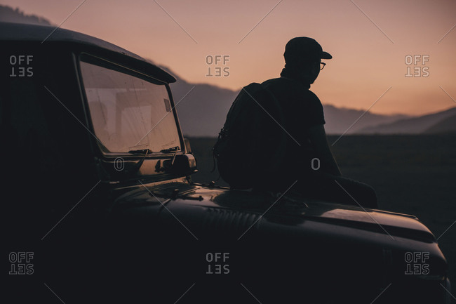 Man standing by hood of car silhouetted against sky at sunset