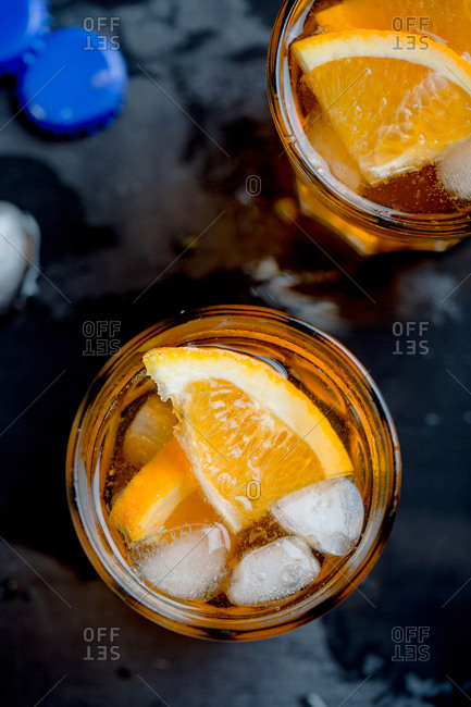 Close up overhead view of fresh bitter sweet cocktail garnished with orange slice