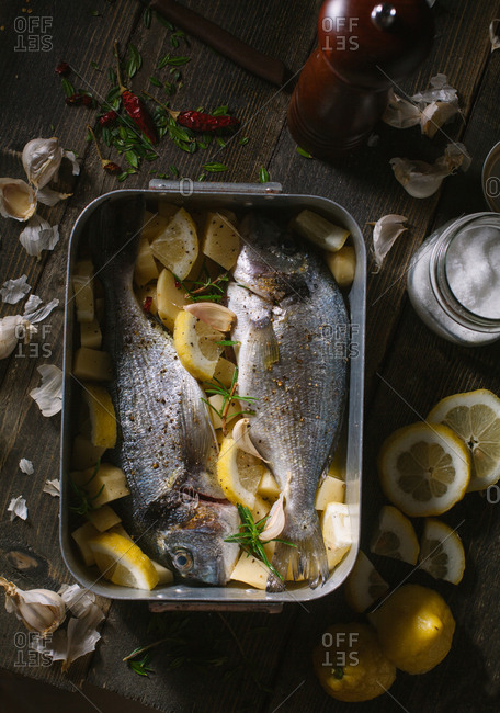 Baking pan with Bream, potatoes and lemon wedges on kitchen table before cooking