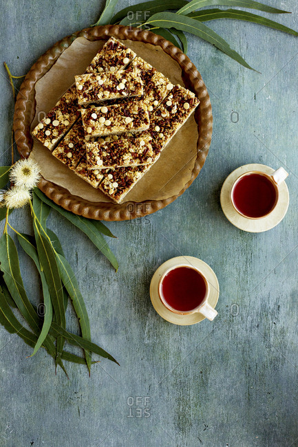 Pecan white chocolate breakfast bars on platter served with cups of hot tea