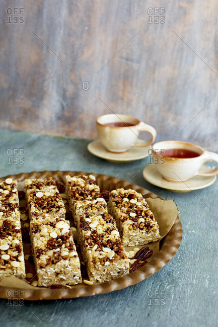 Pecan white chocolate breakfast bars on plate served with cups of hot tea