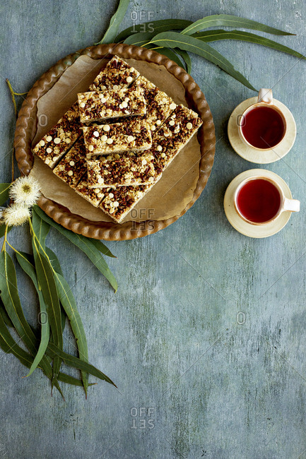 Pecan white chocolate breakfast bars on platter served with two cups of tea