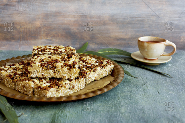 Pecan white chocolate breakfast bars served on plate with hot beverage