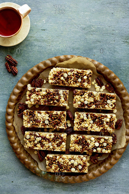 Freshly baked pecan white chocolate breakfast bars served with a cup of tea